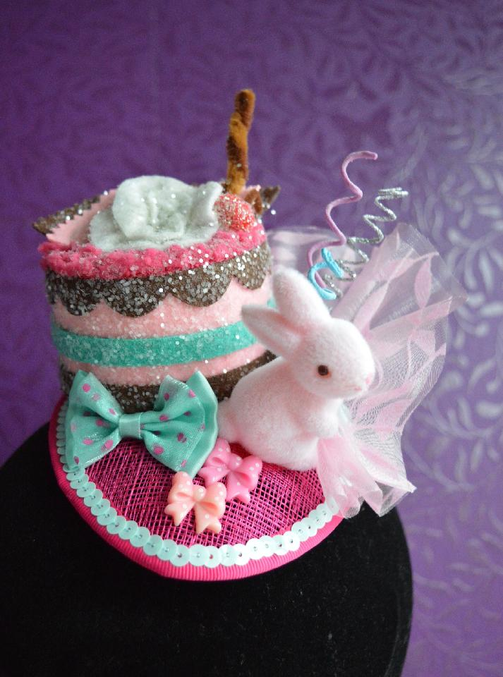 IMAGE - Pink sinamay fascinator with glittered cake and pink bunny. Decorated with pink organza, curly sticks and bows. Fixes to the hair with a comb.