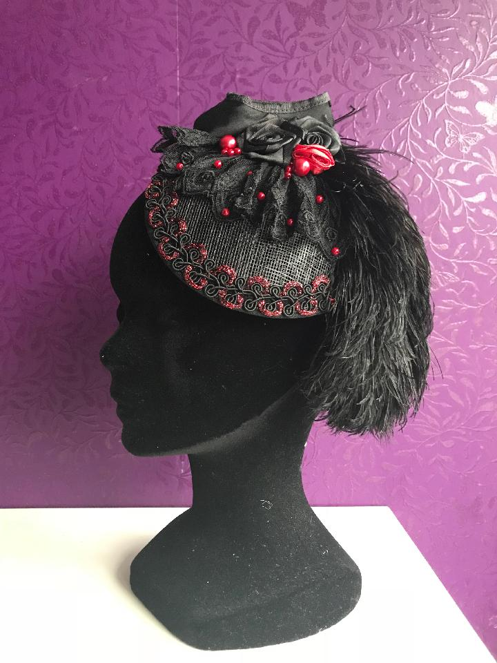 IMAGE - Black sinamay fascinator with black and red trim, black pointeshoe, feathers, vintage lace and ribbonroses. Finished with red pearls. Fixes to the hair with a comb.