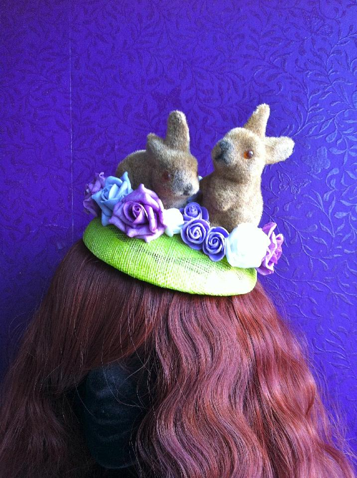IMAGE - Green sinamay fascinator with bunnies and purple foam flowers. Fixes to hair with a comb.