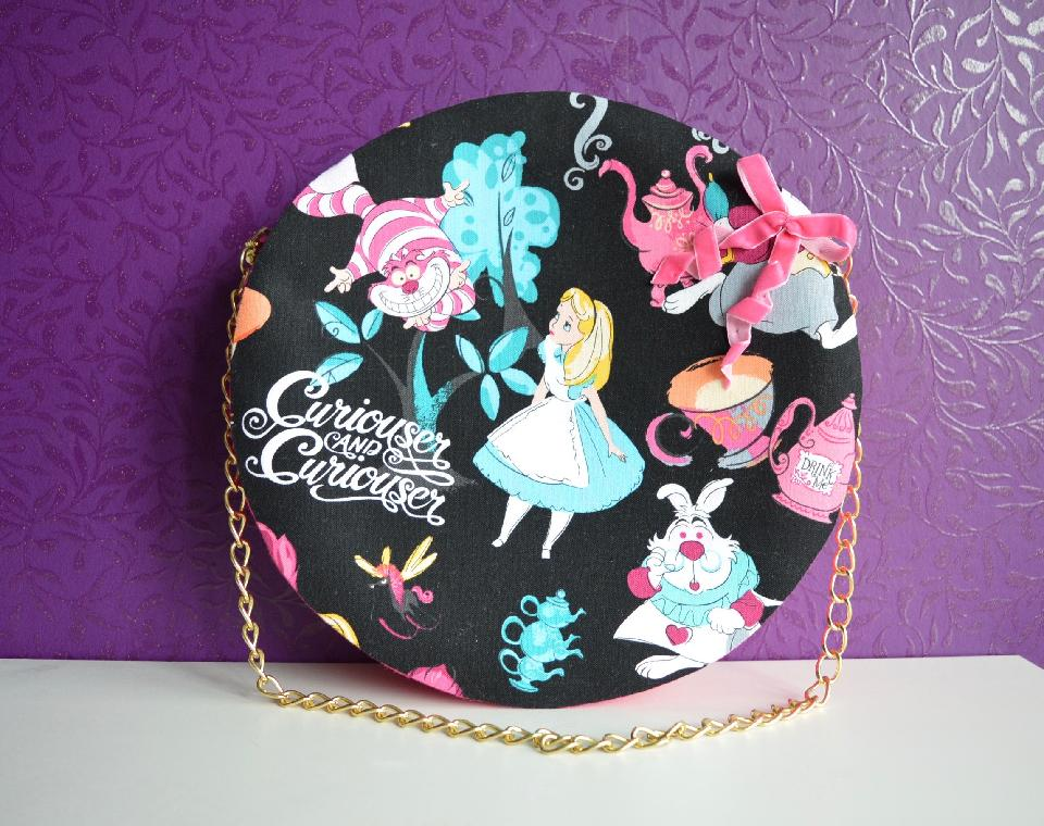 IMAGE - Round hard handsewn handbag with printed Alice in Wonderland fabric. Decorated with pink bow. Has a gold chain and closes with a magnetic clip.