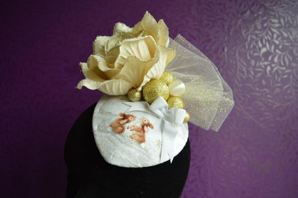 IMAGE - Fabric covered fascinator with gold rose, glittered tulle, gold and cream spheres and white velvet bow. Two bunnies are printed on the fabric. Fixes to hair with a comb.