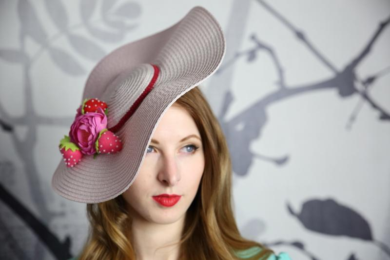 IMAGE - Light pink flat straw hat decorated with a pink flower and handmade felt strawberries. Stays on with an elastic.