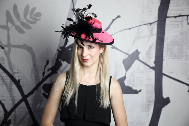 IMAGE - Handblocked hot pink sinamay hat. Brim is finished with black ribbon, on the side is a cluster of black feathers. Stays on with an elastic.