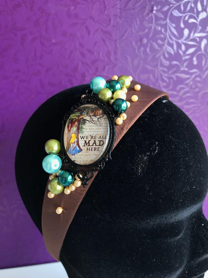 IMAGE - Brown satin headband with cameo featuring Alice and the Cheshire cat, finished with green, blue and cream pearls.