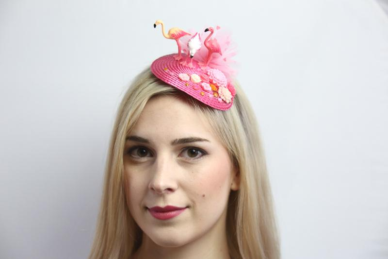 IMAGE - Pink straw fascinator with three flamingos, pink tulle, flower ornaments and rhinestones. Fixes to the hair with a comb.