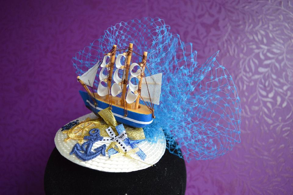 IMAGE - Cream straw fascinator with model ship, blue netting and decorated with gold and blue bows and anchors. Fixes to hair with a comb.