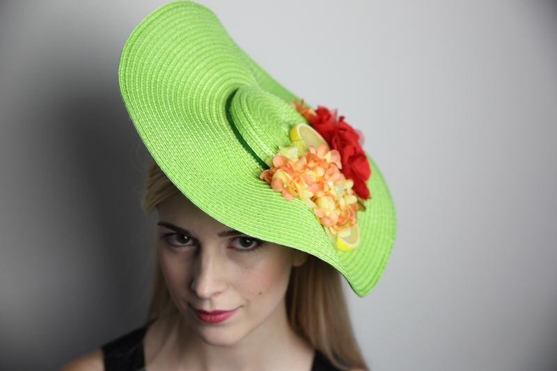 IMAGE - Green straw hat with dark green trim, red and orange flowers and lemons.