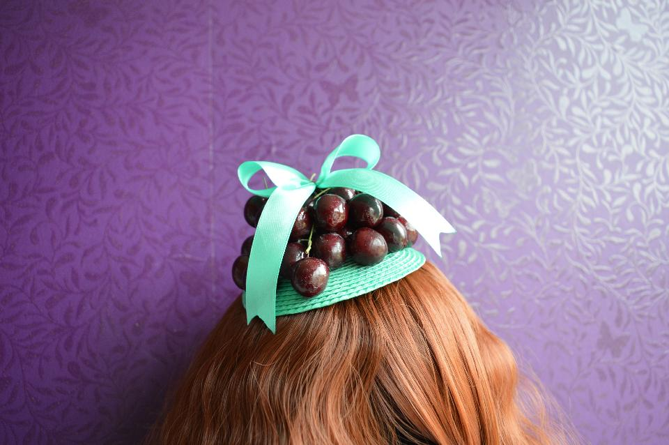 IMAGE - Green fascinator decorated with cherries and green bow. Fixes to hair with a comb.