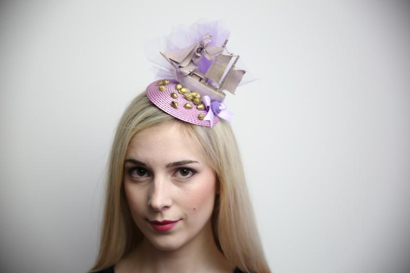 IMAGE - Lilac fascinator with medium sized model shop, painted lilac with gold details. Purple tulle, bow and gold seashells. Fixes to hair with a comb