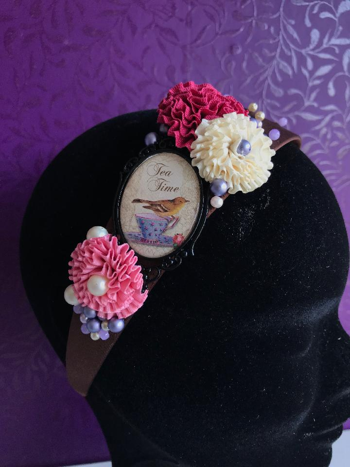 IMAGE - Brown satin headband with bird and teacup drawing. Decorated with pink and cream ribbons, finished with purple and white pearls.