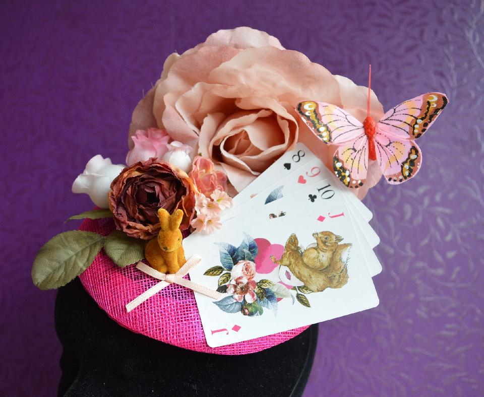 IMAGE - Pink sinamay fascinator with pink flowers, playing cards, bunny and butterfly. Finished with a pink bow. Fixes to hair with a comb.