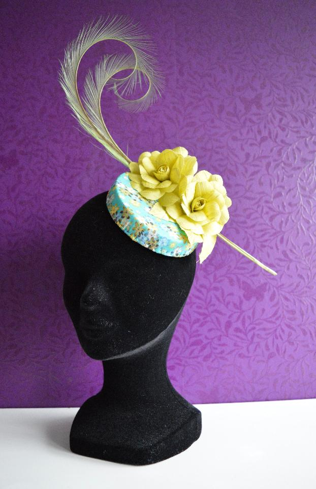 IMAGE - Handblocked fascinator covered in blue and yellow flower print fabirc. Decorated with curled feathers and two handmade flowers. Fixes with wigclips.
