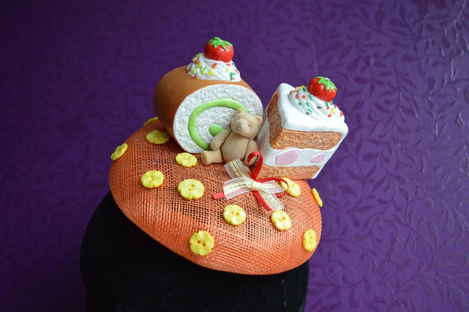 IMAGE - Orange sinamay fascinator with two pieces of cake and a bear. Decorated with bows and yellow flower buttons. Fixes to hair with a comb.