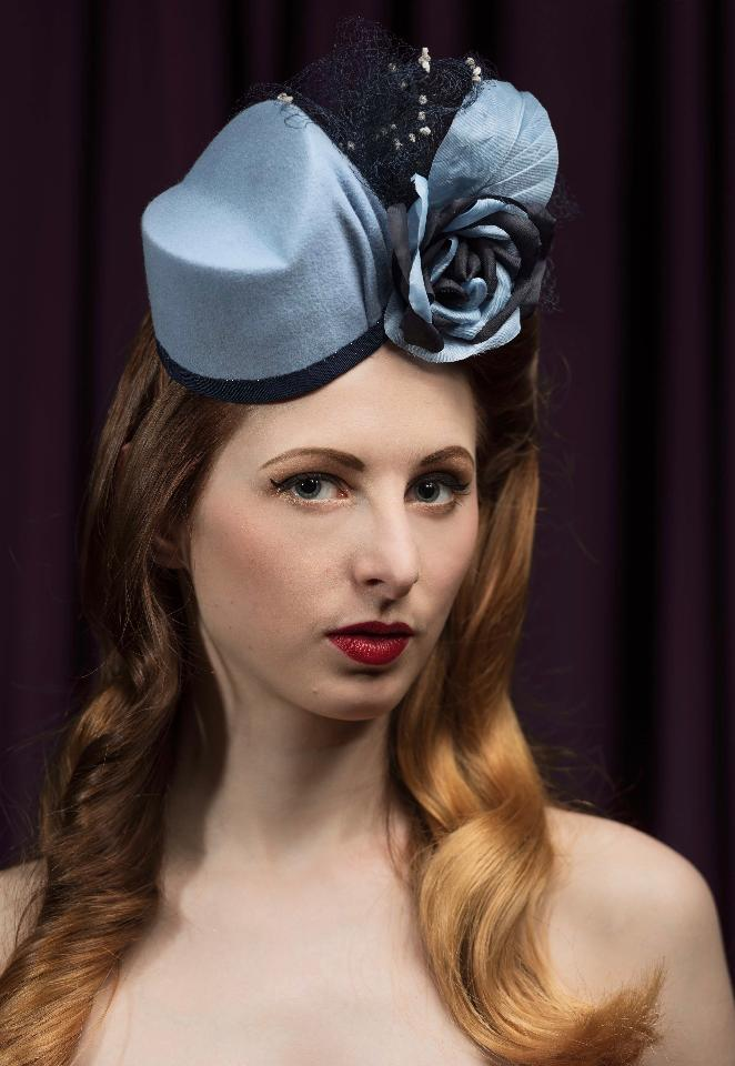 IMAGE - Handblocked light blue velour felt fascinator. Finished with navy ribbon, pleats, navy net and handmade slik rose. Fixes to hair with an elastic.