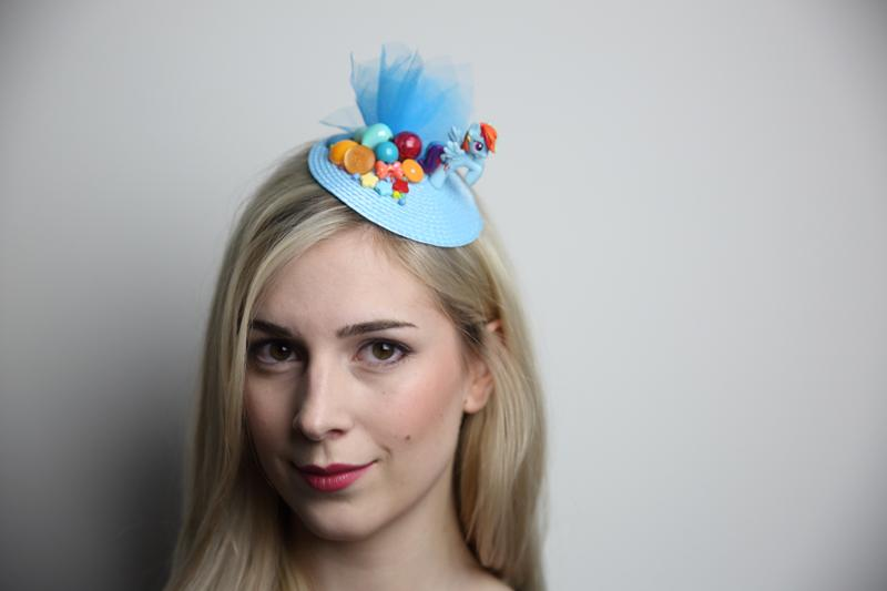 IMAGE - Light blue straw fascinator with tulle, pony and decorated with rainbow colored beads and buttons. Fixes to hair with a comb.