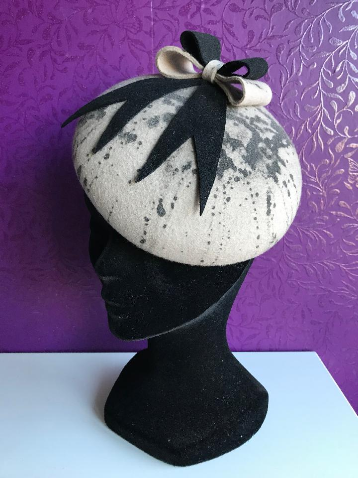 IMAGE - Handblocked felt baretstyle fascinator. The cream coloured felt has black paintsplatters, decorated with a black and cream felt bow. Stay on the head with an elastic.
