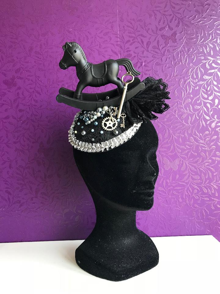 IMAGE - Black sinamay fascinator with black rockinghorse, black vintage lace, silver gears and keys. Finished with silver ruffle trim and silver pearls. Fixes to the hair with a comb.