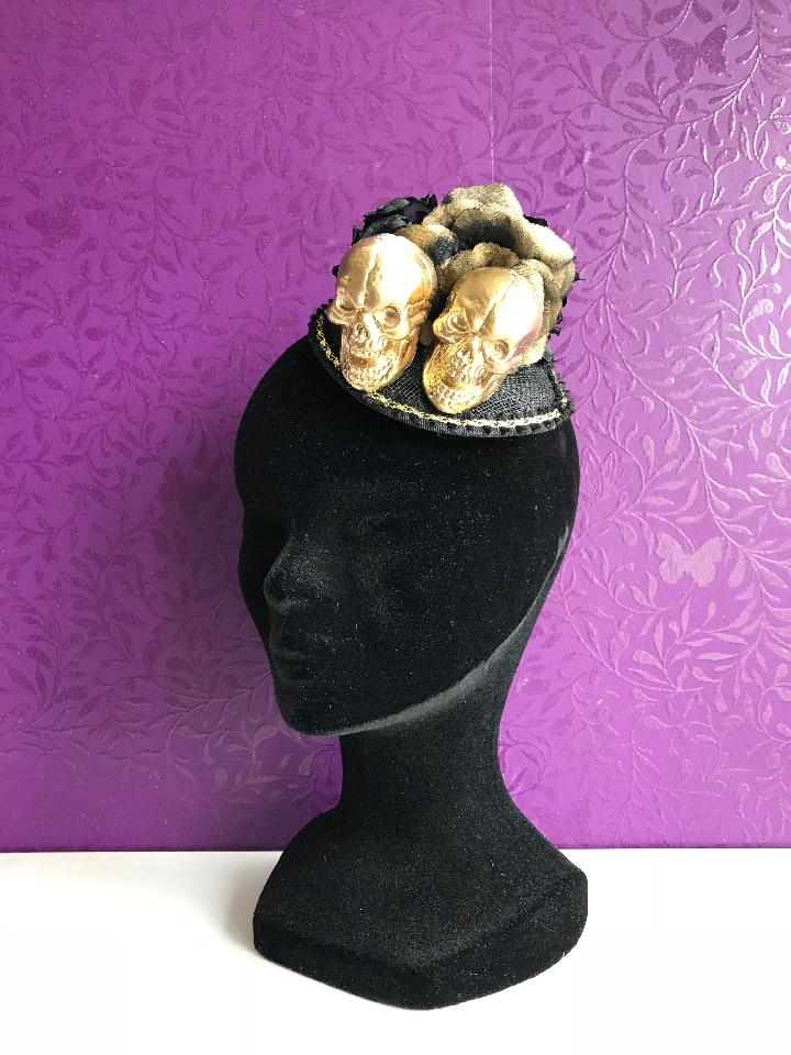 IMAGE - Black sinamay fascinator with gold trim, gold skulls and black flowers. Fixes to the hair with a comb.