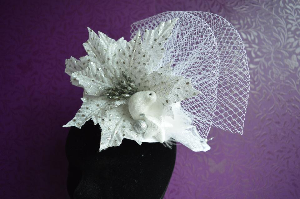 IMAGE - White straw fasinator with white and silver hellebore and bird. Finished with white netting and glittered spheres. Fixes to hair with a comb.