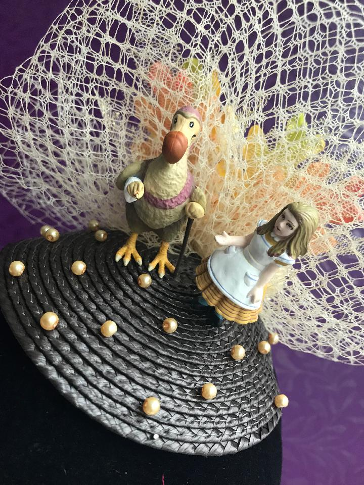IMAGE - Brown straw fascinator with cream netting and pearls, featuring Alice and the Dodo. Finished with orange flowers. Fixes to the hair with a comb.