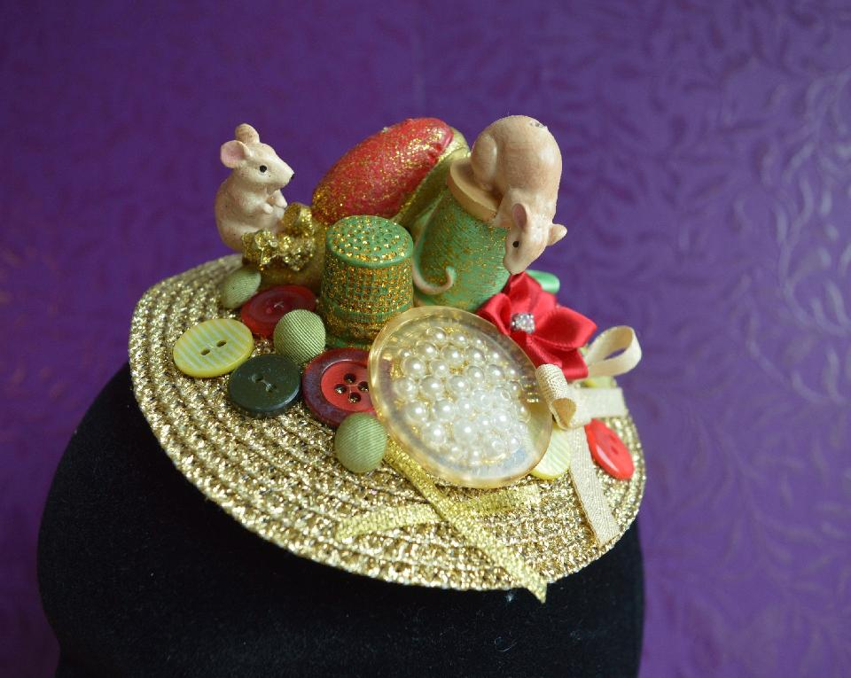 IMAGE - Gold straw fascinator decorated with sewing mice, and buttons in various shades of gold, green and red. Fixes to hair with a comb.