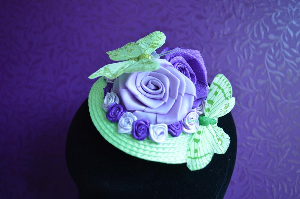 IMAGE - Green straw fascinator decorated with purple and lilac ribbon roses and green butterflies. Fixes to hair with a comb.