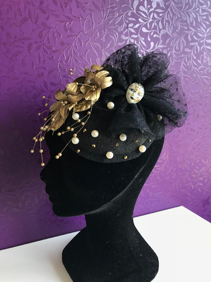 IMAGE - Black sinamay fascinator with gold flowers, black lace and porcelain mask. Finished with ivory pearls and gold rhinestones. Fixes to the hair with a comb.