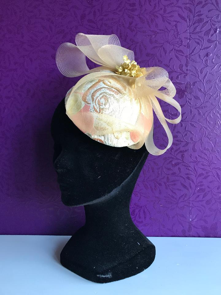 IMAGE - Handblocked fascinator coverd with peach and gold fabric. Decorated with gold horsehair bow and gold flowers. Fixes to the hair with a wigclip.