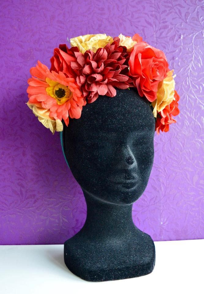 IMAGE - Green satin headband covered in red, orange and gold flowers. This headband is very full.