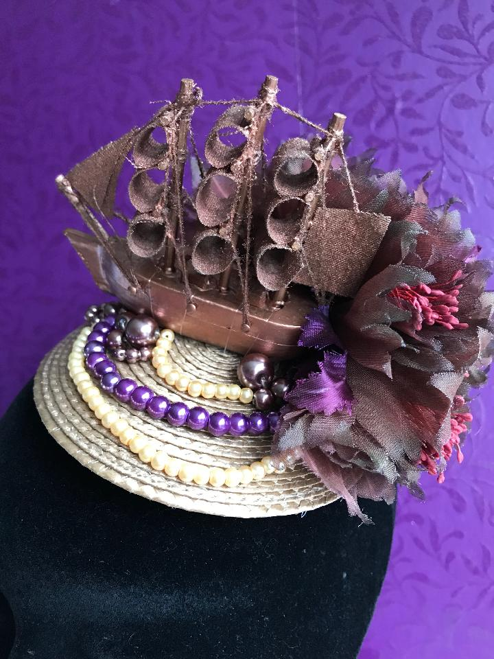 IMAGE - Light brown straw fascinator with copper boat, brown flowers and cream and purple pearls. Fixes to the hair with a comb.