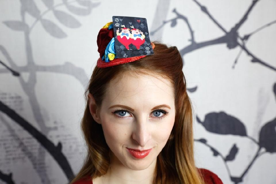IMAGE - Red straw fascinator decorated with red, blue and yellow ribbon roses and playingcard featuring Tweedledee and Tweeldedum. Fixes to hair with a comb.