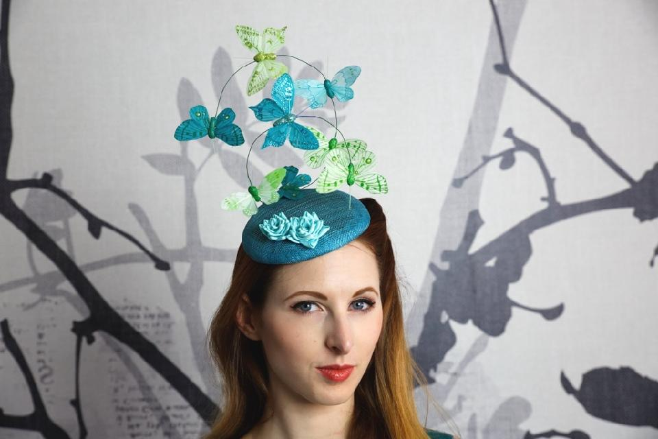 IMAGE - Teal sinamay fascinator with teal and applegreen butterflies on wire. Finished with lightblue folded ribbon flowers. Fixes to hair with a comb.