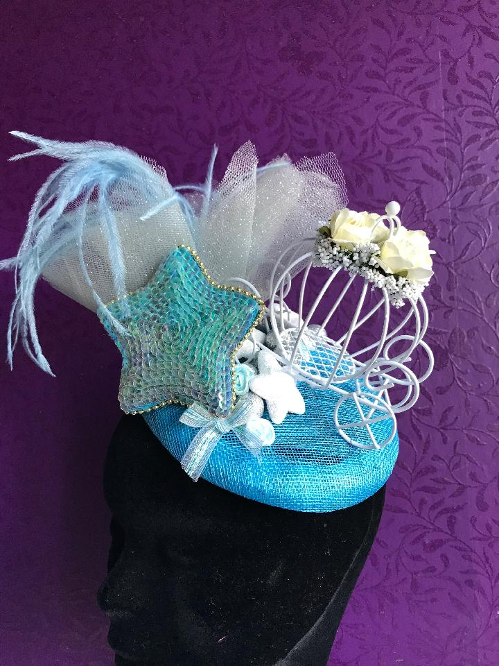 IMAGE - Bright blue sinamay fascinator with silver tulle, blue feathers, white carriage, blue sequin star and silver glittered spheres. Fixes to the hair with a comb.