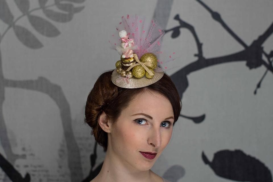 IMAGE - Cream straw fascinator with cute pink poodle sitting on macarons. Decorated with pink tulle and gold glittered spheres and a bow. 