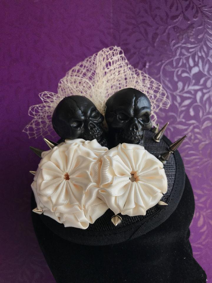 IMAGE - Black sinamay fascinator with black skulls, cream netting, cream ribbon ornaments and silver spikes. Fixes to the hair with a comb.