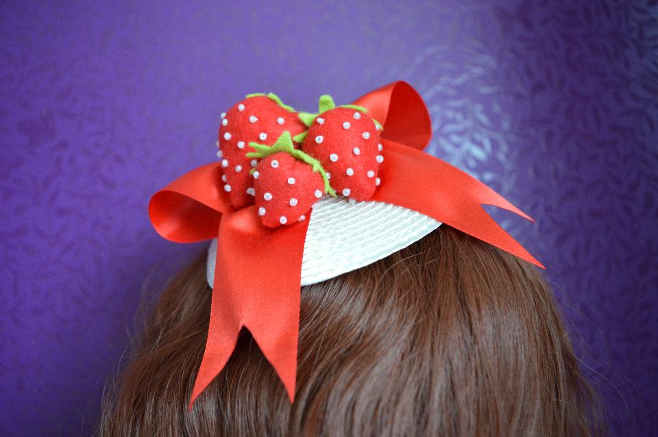 IMAGE - White fascinator with red satin bow and felt handmade strawberries. Fixes to hair with a comb.