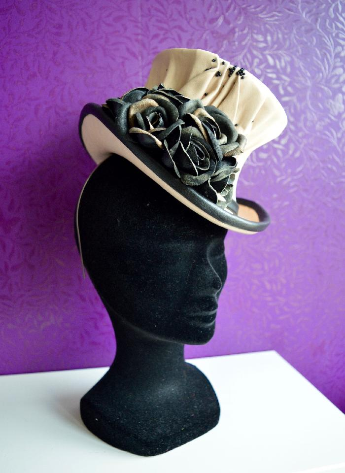 IMAGE - Handblocked cream leather tophat. The Leather has been draped over the shape to create an intricate design. Decorated with handmade black leather roses, black leather binding and little black glass beads. Stays on with a thin metal headband and a wigclip for extra support.