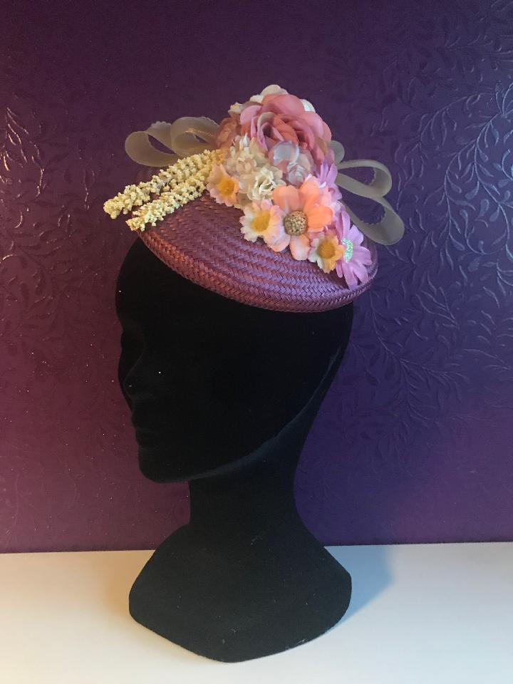 IMAGE - Purple straw fascinator with cream crinoline bow and various pink and cream flowers. Fixes to the hair with a comb.