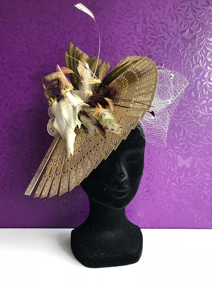 IMAGE - Black sinamay fascinator with gold fan, green vintage netting, various feathers and skull, finished with gold lace. The feathers and skull are real but repurposed from vintage pieces, no new animals have been killed for this piece. Fixes to the hair with a comb and elastic.