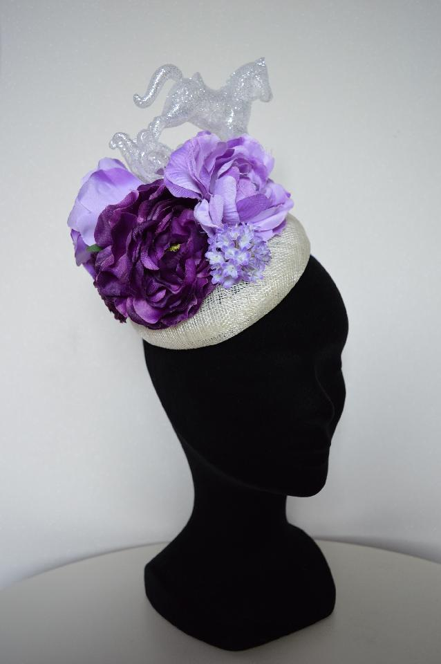 IMAGE - Cream sinamay fascinator decorated with lilac and purple flowers and glittered rockinghorse. Fixes to hair with a comb, extra hat elastic has been added for support.