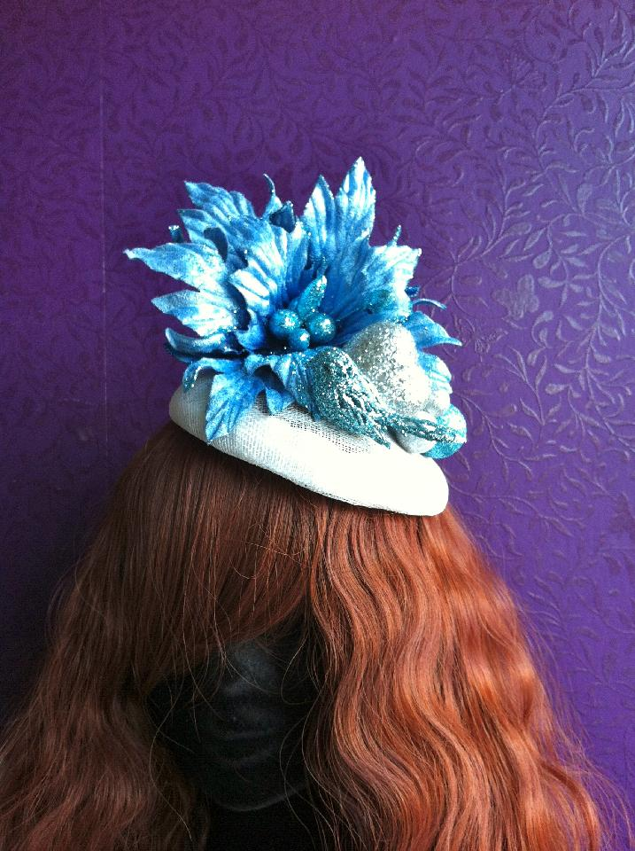 IMAGE - Grey sinamay fascinator with blue glittered flower and bird. Back is finished with blue and silver glittered spheres. Fixes to hair with a comb.