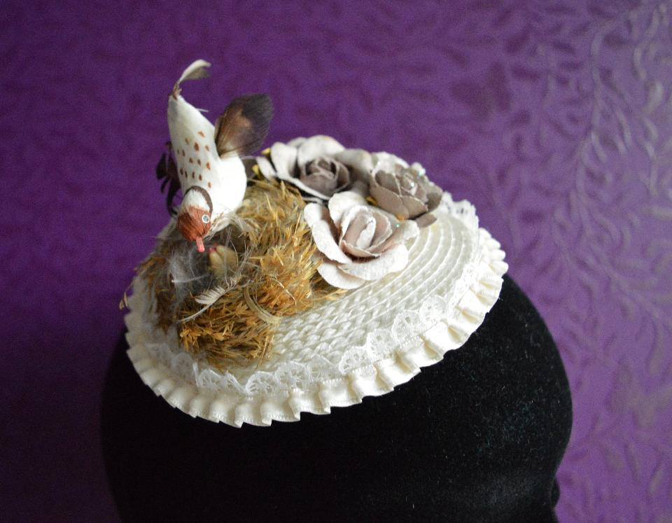 IMAGE - Off-white fascinator with lace border. Decorated with bird and paper flowers. The flowers are very sturdy but should not get wet. Fixes to hair with a comb.
