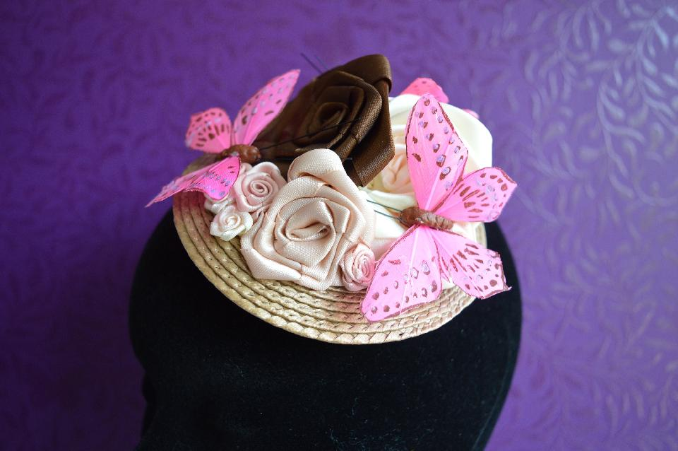 IMAGE - Light brown fascinator decorated with brown ribbon roses and pink butterflies.
