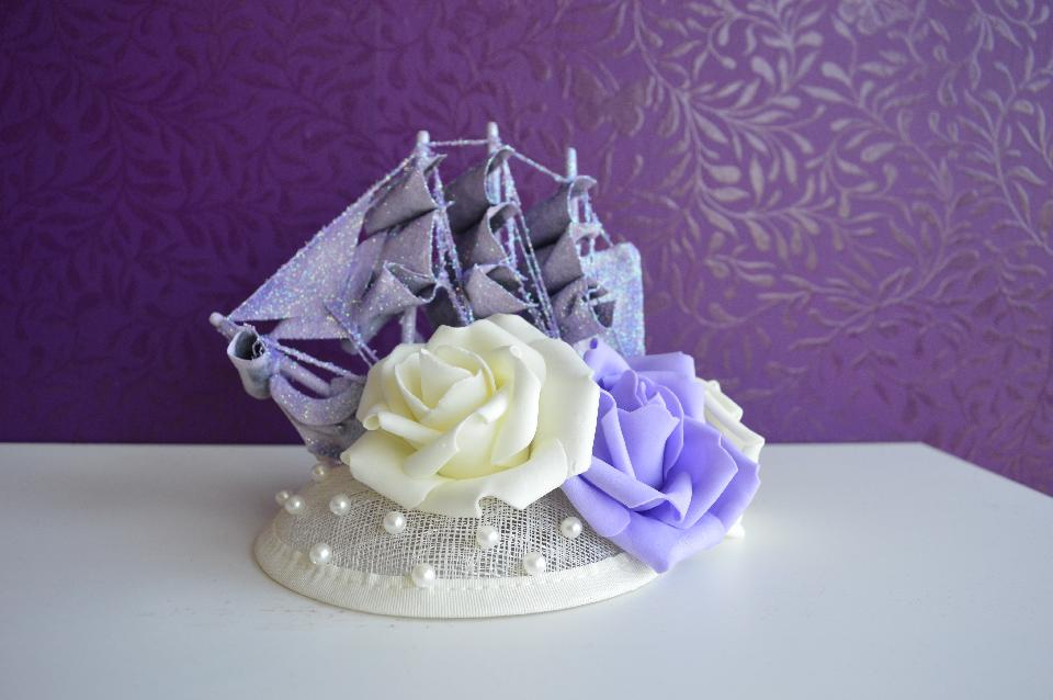 IMAGE - Off-white sinamay fascinator with lilac glittered boat, white and lilac foam flowers and pearls. Fixes to hair with a comb.