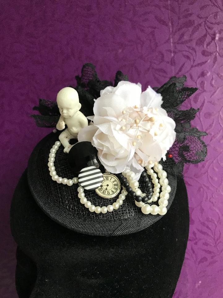 IMAGE - Black sinamay fascinator with antique porcelain doll, vintage black lace, vintage white flowers, buttons, clock charm and black and white pearls. Fixes to the hair with a comb.