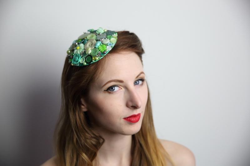IMAGE - Green fascinator covered in buttons and pearls. 